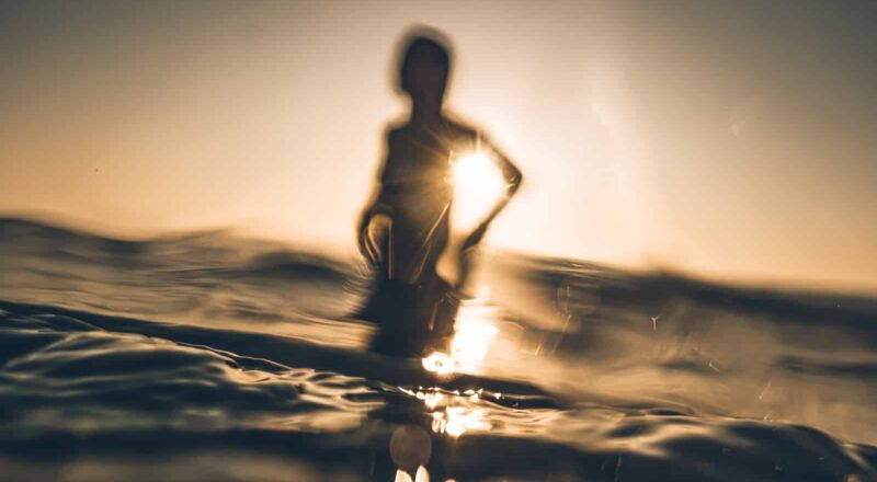 silhouette of person standing on sea wave during daytime