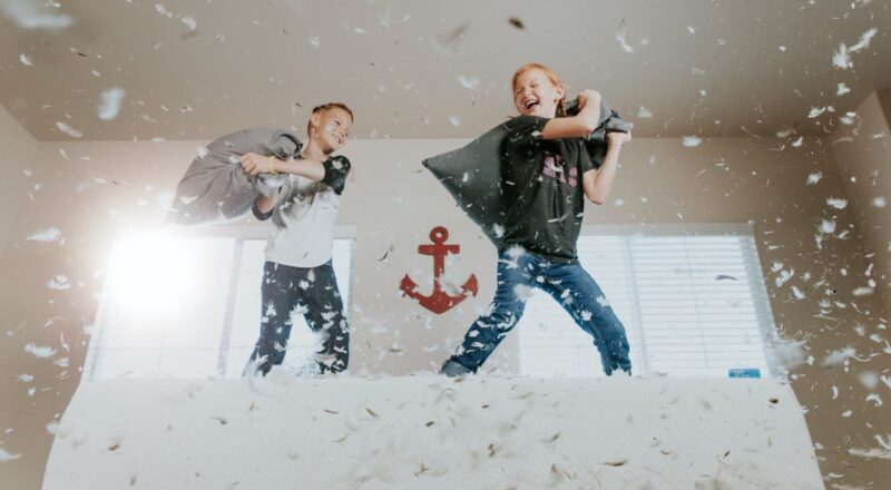 two toddler pillow fighting