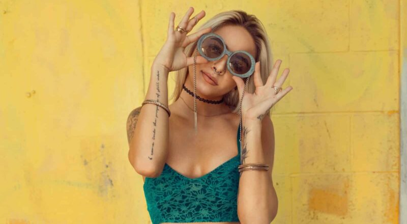 woman in blue bralette holding sunglasses putting on her eyes