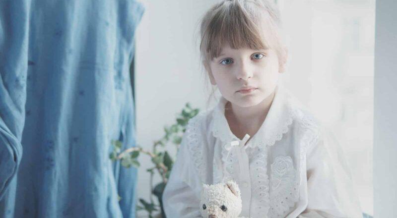 girl in white dress holding white bear plush toy